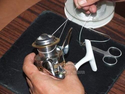 将纺车轮的线杯架打开后,把我们刚绑好的活套套在线杯上。如图所示。